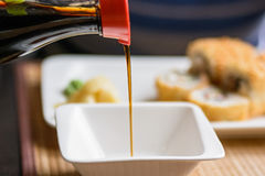 Pouring soy sauce in white bowl. Close up pouring soy sauce in white bowl before eating Japanese food in restaurant Stock Photo