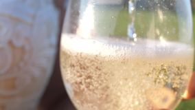 Pouring sparkling wine from bottle into transparent glasses. glass of champagne in hand of girl sparkles and foams in. Sun. closeup. teamwork of loving couple stock video