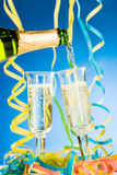 Pouring sparkling wine. A bottle and two glass of sparkling wine, streamers and blue background royalty free stock photo