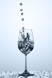 Pouring and splashing cleaner drinking water on a wineglass while standing against light background. Royalty Free Stock Photography