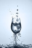 Pouring and splashing cleaner drinking water on a wineglass while standing against light background. Royalty Free Stock Photos