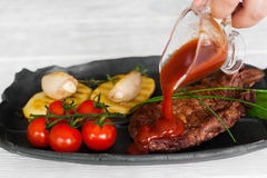 Pouring steak with ketchup, meat and garnish meal stock photography