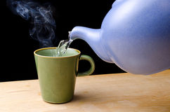 Pouring steaming hot tea in a cup Stock Image