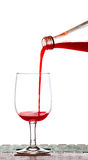 Pouring Strawberry juice from bottle into glass Royalty Free Stock Images
