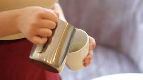Pouring stream milk, barista prepares latte in cup stock video