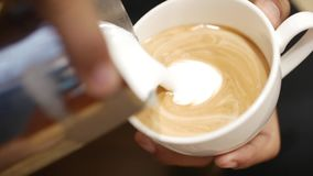 Pouring stream milk into a cup of espresso. Close-Up. Stock footage.