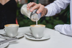 Pouring sugar into cappucino Royalty Free Stock Image