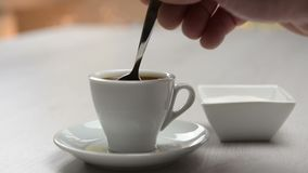 Pouring sugar in coffee cup