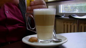 Pouring sugar into coffee latte. Man at a cafe table pouring white sugar into his coffee latte clear glass mug stock video