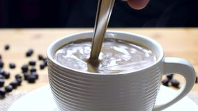 Pouring sugar into a cup of coffee and mix. 4k stock video