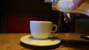 Pouring sugar into a cup from dispenser. Cafe scene. Close up of hand holding sugar dispenser pouring sugar into white cup on a saucer with steaming tea or stock video footage