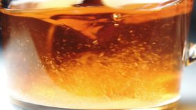 Pouring a sugar into a cup of tea. And stirring with a spoon. Slow motion stock video