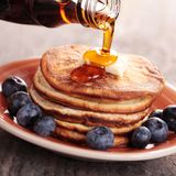 Pouring syrup. Close-up of pouring maple syrup on stack of pancakes Stock Image