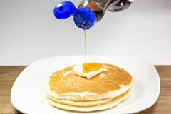 Pouring Syrup From A Blue Tip Bottle Onto The Square Of Butter On A Stack Of Golden Pancakes Waiting To Be Eaten Royalty Free Stock Images