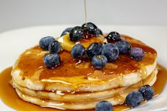 Pouring syrup over the butter on the blueberry stack of pancakes on the kitchen table waiting to be eaten stock photography