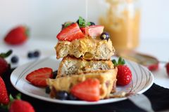 Pouring syrup over french toasts with peanut butter, strawberries and blueberries. royalty free stock image