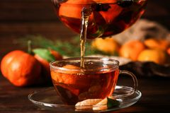 Pouring tangerine tea into cup. On wooden background Royalty Free Stock Photography