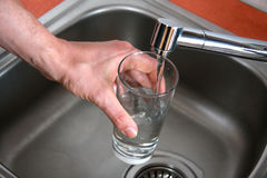 Pouring tap water by man's hand Royalty Free Stock Photo