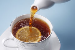 Pouring tea. Stock image of the pouring hot tea to the tea cup Royalty Free Stock Image