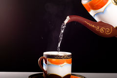 Pouring tea. From porcelain tea-kettle into white cup Royalty Free Stock Photo