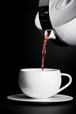 Pouring tea on black background. Close-up shot of pouring tea on black background Stock Photography