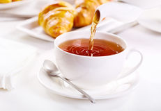 Pouring tea Stock Images