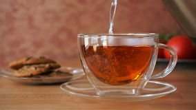 Pouring tea into a cup stock footage