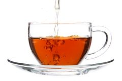 Pouring Tea into Cup with Splash. Isolated Stock Photo