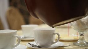 Pouring tea into cup on table from clay kettle steaming stock video
