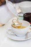 Pouring tea into cup of tea Stock Photos