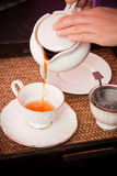 Pouring tea into cup of tea Stock Images