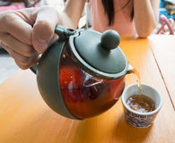 Pouring tea into cup of tea Stock Photo