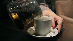 Pouring tea into cup of tea stock video footage