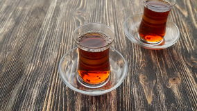 Pouring tea into a cup on a wooden table. Close up detailed view of teapot pouring hot black tea into the glass stock video footage