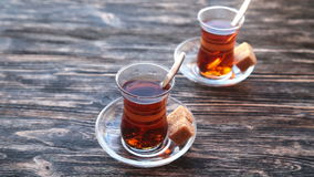 Pouring tea into a cup on a wooden table. Close up detailed view of teapot pouring hot black tea into the glass stock footage