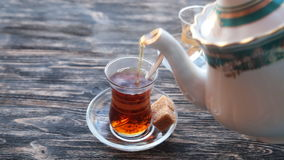 Pouring tea into a cup on a wooden table. Close up detailed view of teapot pouring hot black tea into the glass stock video