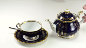 Pouring tea into porcelain cup stock footage