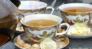 Pouring tea from porcelain tea-kettle into cup. Royalty Free Stock Image