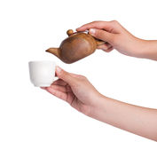 Pouring tea into tea cup over white background Stock Images