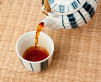 Pouring tea from the teapot Stock Images