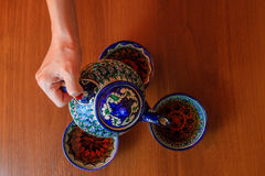 Pouring tea from teapot. Traditional uzbek tea ceremony accessories Royalty Free Stock Images