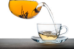 Pouring tea from teapot on wooden over white background, close u Stock Photos