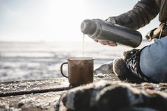 Pouring the tea from the thermos. Outdoors. Cold snow and spring light stock photography