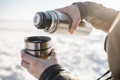 Pouring the tea from the thermos. Outdoors. Cold snow and spring light stock images
