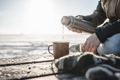 Pouring the tea from the thermos. Outdoors. Cold snow and spring light stock image