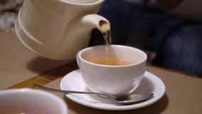 Pouring tea to cup from teapot. Pouring tea to cup from white teapot stock video footage