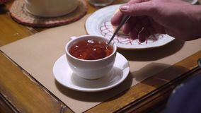 Pouring tea to cup from teapot. Pouring tea to cup from white teapot stock footage