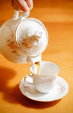 Pouring tea to a teacup Stock Images