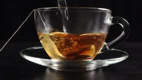 Pouring a tea in transparent cup with hot water and teabag, slow motion. Pouring a tea in transparent cup with hot water and teabag on black background, slow stock footage