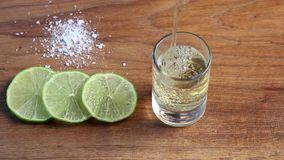 Pouring tequila in glass with lime slices and salt stock footage